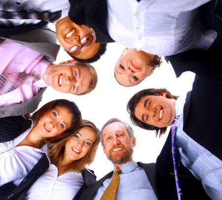 from below: Group of business people standing in huddle