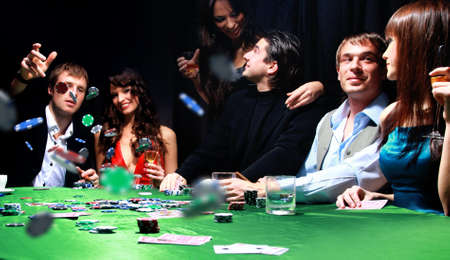 casinos: Young man throwing chips on the table while playing cards