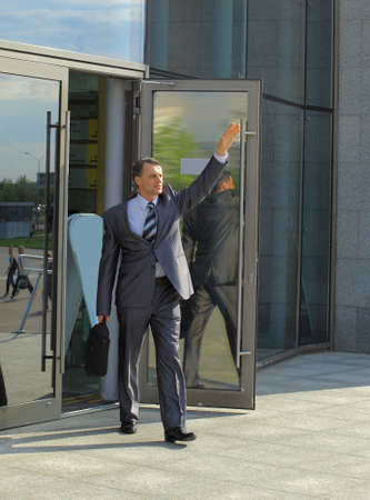hailing: Smart young businessman hailing a taxi cab outside a office