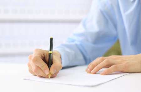 write a letter: Hands writing on a paper