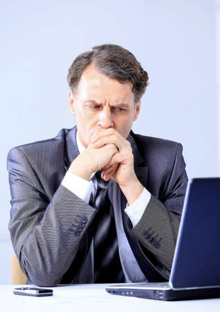 Thoughtful businessman looking at his laptop  photo