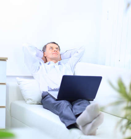 Senior man in sofa with laptop computer  photo