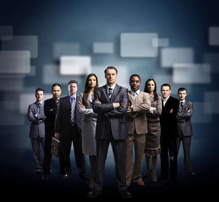 liderazgo: equipo comercial formado por j�venes empresarios de pie sobre un fondo oscuro