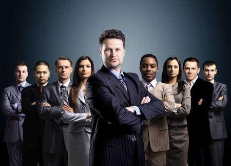 lideres: equipo de negocios formada por jóvenes empresarios de pie sobre un fondo oscuro Foto de archivo