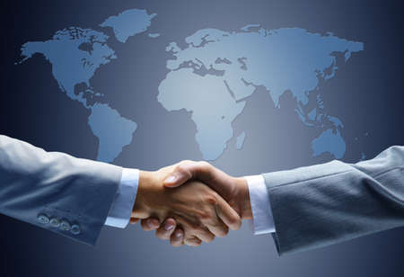 business people shaking hands: Handshake with map of the world in background  Stock Photo