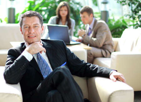 Senior business relaxed on a chair with his colleagues at a meeting in the back  photo