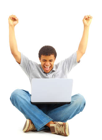 Happy young man working on a laptop, isolated against white background  photo
