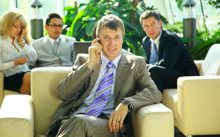 business man speaking on the cell phone while in a meeting  photo