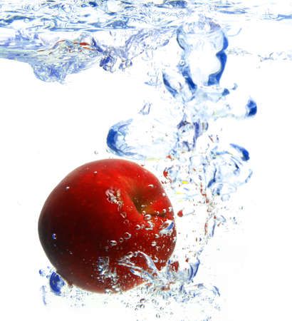 red apple under water with a trail of transparent bubbles.  photo
