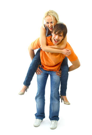 Happy young female enjoying a piggyback ride on boyfriends back against white photo