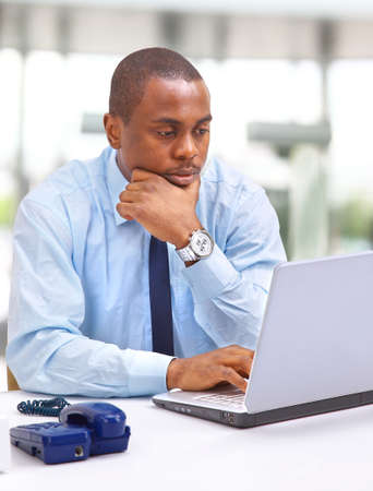 Portrait of a happy African American entrepreneur displaying computer laptop photo