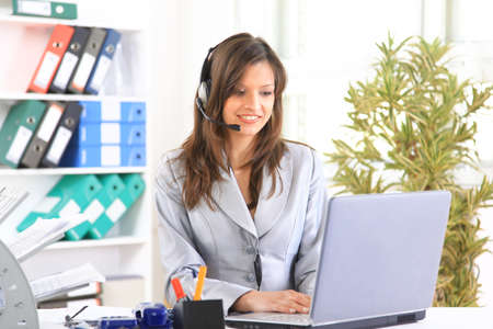 Portrait of a beautiful business woman working at her desk with a headset and laptop Stock Photo - 11315137