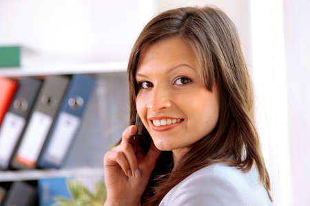 Happy woman calling on phone at home office