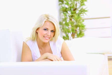 divan: Sonriente ni�a acostada en div�n y el pensamiento Foto de archivo