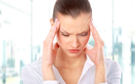 Young woman suffering a headache over white background photo
