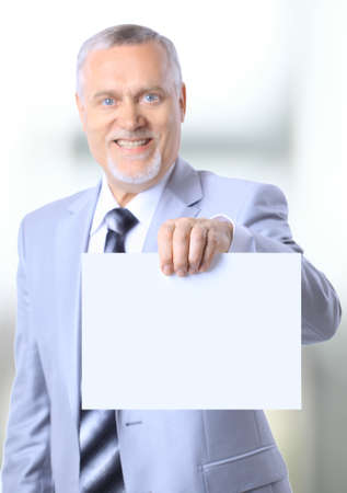 Portrait of a happy mature businessman showing an emty bill board against white background  photo