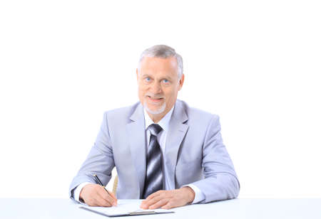 writing materials: Portrait of a handsome mature business executive at work
