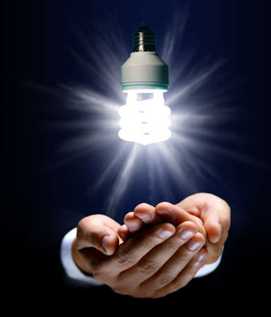 Glowing lightbulb and hand  photo