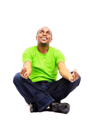 African American man sitting in yoga position on white background  photo