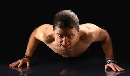 Muscular male kick-boxer doing push-up on his knuckles  Stock Photo - 11315760