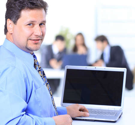 Portrait of a happy man entrepreneur displaying computer laptop in office  photo