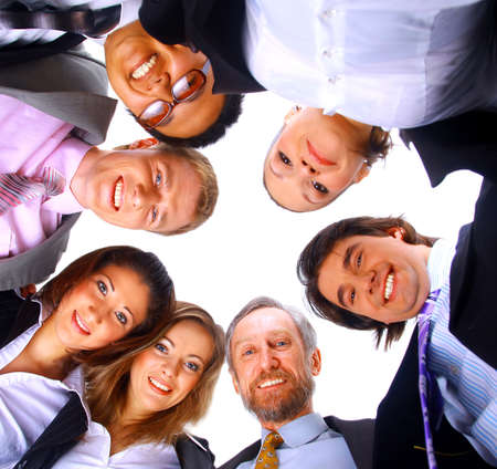 business leader: Group of business people standing in huddle, smiling, low angle view  Stock Photo