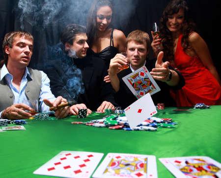 cartas de poker: Hombre elegante en traje negro se pliega en dos cartas del póker del casino en Las Vegas sobre negro