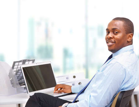 Portrait of a happy African American entrepreneur displaying computer laptop on white background photo