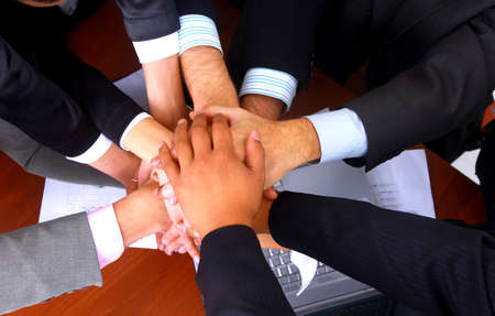 group of business people making a pile of hands in a light and modern office environment   photo