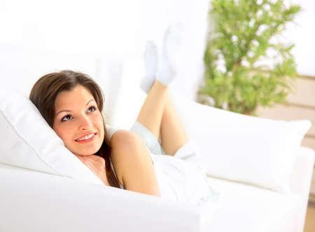 divan: Sonriente ni�a acostada en el div�n y pensando Foto de archivo