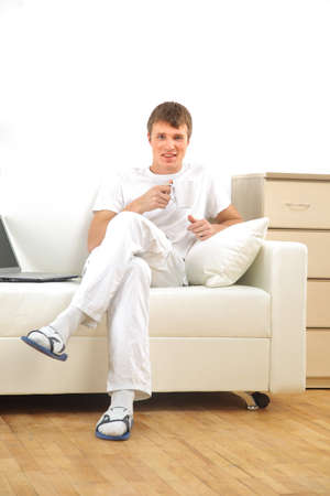 Smiling young man working on laptop computer at home Stock Photo - 11320406