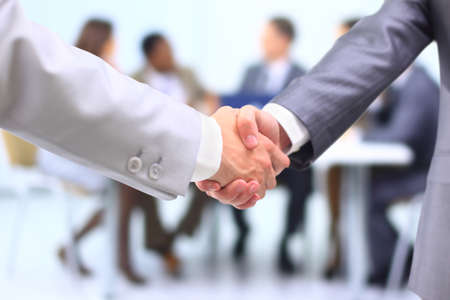 Two successful businessman shaking hands in front of corporate team at office  photo