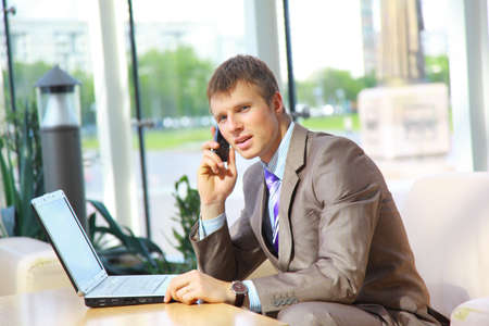 Businessman sitting at table in office hall, talking on mobile phone and using laptop computer  photo
