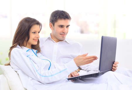 computer model: Portrait of a happy young couple sitting on a sofa using laptop