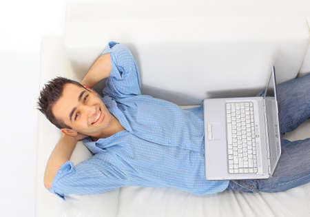jeune mec: Portrait d'un jeune homme de d�tente sur le canap� avec un ordinateur portable Banque d'images