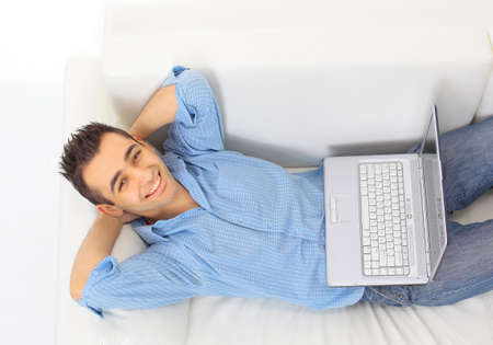 imagining: Portrait of a young guy relaxing on couch with a laptop