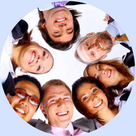 Group of business people standing in huddle, smiling, low angle view photo
