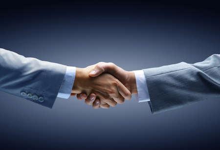 negotiating: Handshake - Hand holding on black background