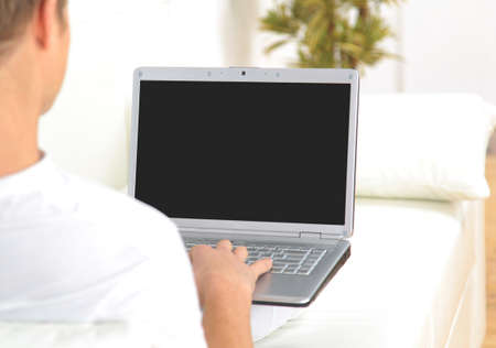 Rear view closeup of a young man working of a laptop  photo