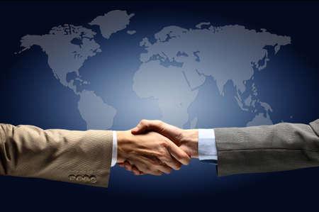 verdrag: Handdruk met kaart van de wereld op de achtergrond