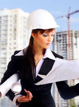 Smiling young female architect holding blueprints isolated on white background  photo