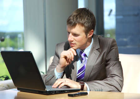 mature businessman: Businessman working on laptop computer at office lobby