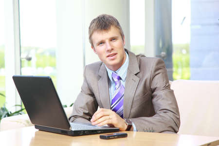 Businessman working on laptop computer at office lobby