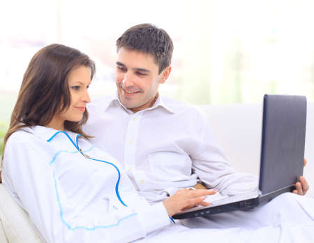 Portrait of a happy young couple sitting on a sofa using laptop Stock Photo - 11479899
