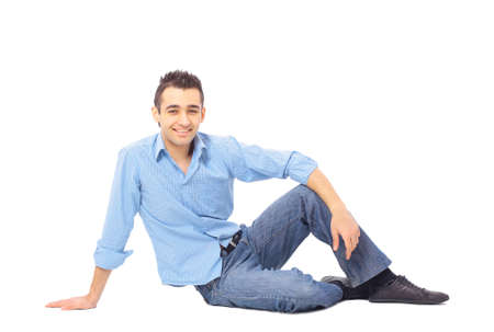 sitting on floor: relaxed man sitting on the floor over white