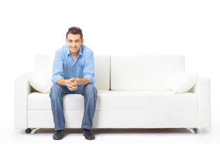 sitting man: Portrait of the young man in white on sofa