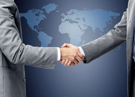 business people shaking hands: handshake over world map