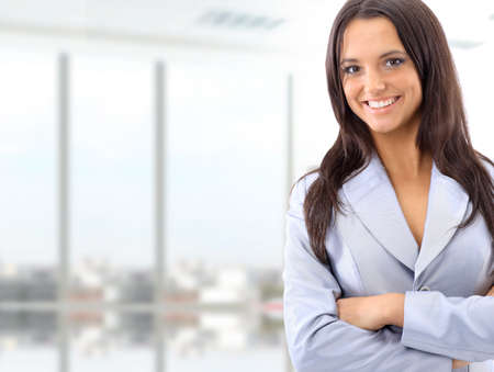 Portrait of a cute young business woman smiling, in an office environment Stock Photo - 11481226