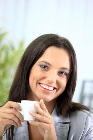 Portrait of a smart young businesswoman reading paper and drinking coffee at office photo