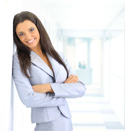 portrait of beautiful businesswoman leaning against white wall in office  photo